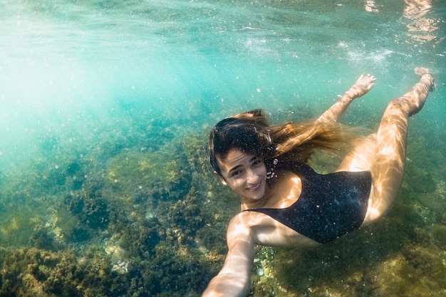 Underwater shot of woman diving Free Photo