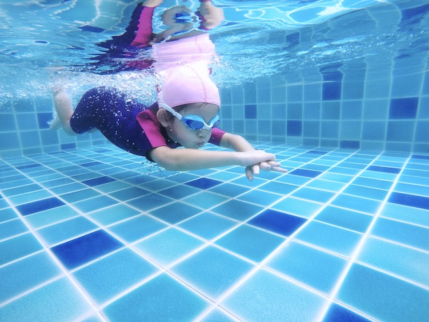 Underwater young little cute girl is swimming in the swimming pool with her swimming teacher Premium Photo