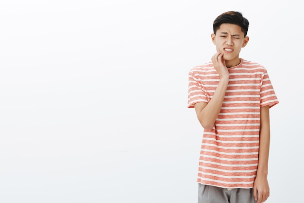 Uneasy attractive young asian male student having tooth decay touching cheek reacting on pain, having rotten teeth Free Photo