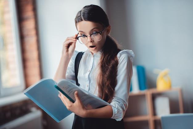 Неожиданные результаты. брюнетка в очках держит отчет и выглядит потрясенной Premium Фотографии