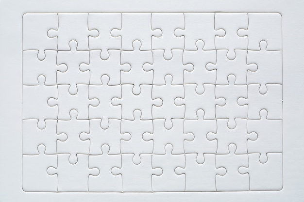 Unfinished red with white jigsaw puzzle pieces Free Photo