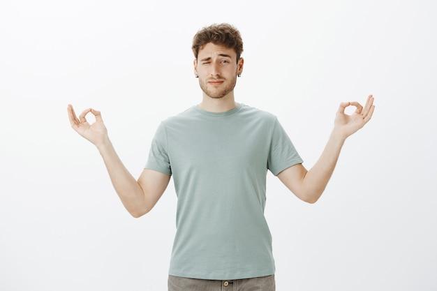 Uomo adulto divertente sfocato con setole in orecchini, sbirciare con un occhio mentre in piedi con le mani aperte in gesto zen e praticare yoga o meditazione Foto Gratuite