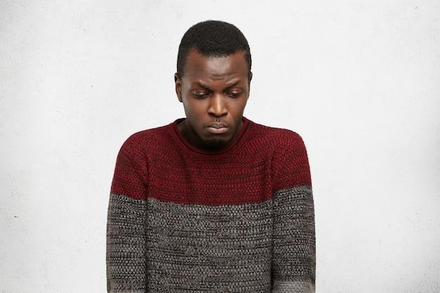 不幸なアフロアメリカンの学生は、大学で問題を抱えながら、悲しそうな表情を見下ろし、不快で恥ずかしい思いをしています。動機と怒りのない悲しい若い黒人男性の肖像画 無料写真