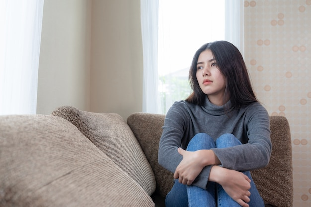 Unhappy asian pretty young woman siting alone on couch with feeling sadness Free Photo