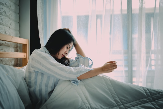 Unhappy asian woman sitting on a bed Premium Photo