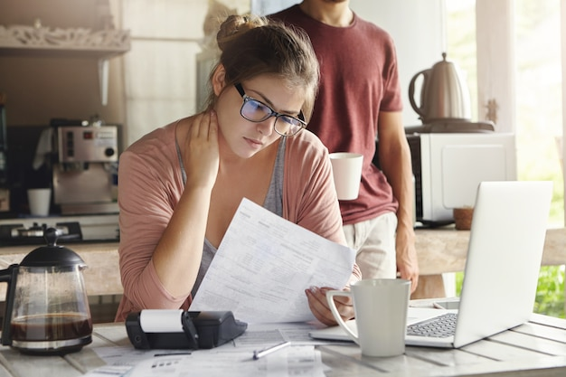 Unhappy beautiful woman wearing spectacles having concentrated look reading notification form bank on debt, sitting at kitchen table in front of open laptop Free Photo