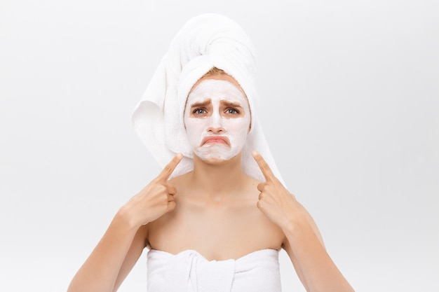 Unhappy beautiful young woman with white clay face mask makes acne therapy, wears white towel on hair, posing against white studio wall. Premium Photo