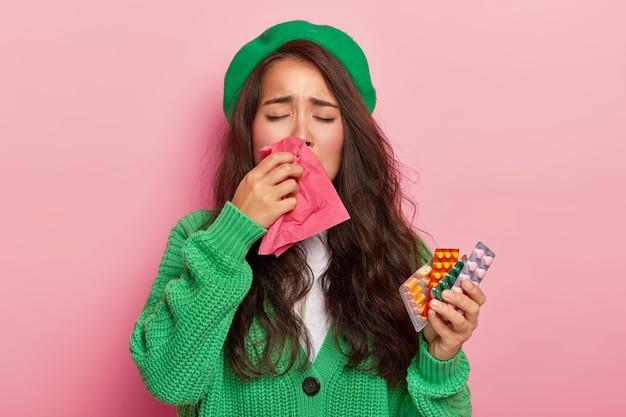 Infelice ragazza bruna soffre di sintomi influenzali, si strofina il naso con il fazzoletto, ha il raffreddore, tiene le pillole, indossa un maglione e un berretto verdi, isolato sul muro rosa Foto Gratuite
