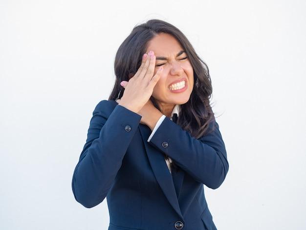 Unhappy businesswoman feeling neck pain Free Photo