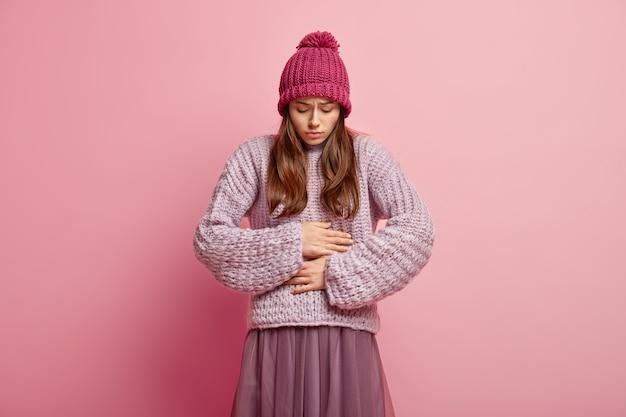 불행한 백인 여성은 양손을 뱃속에 유지하고, 상한 음식을 먹고, 뱃속에 불쾌감을 느끼고, 퐁퐁, 니트 점퍼 및 주름 치마가 달린 분홍색 모자를 쓰고 분홍색 벽 위에 선다. 무료 사진