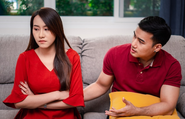 Unhappy couple sitting beside each other on the sofa and avoid talking or quarrel Premium Photo