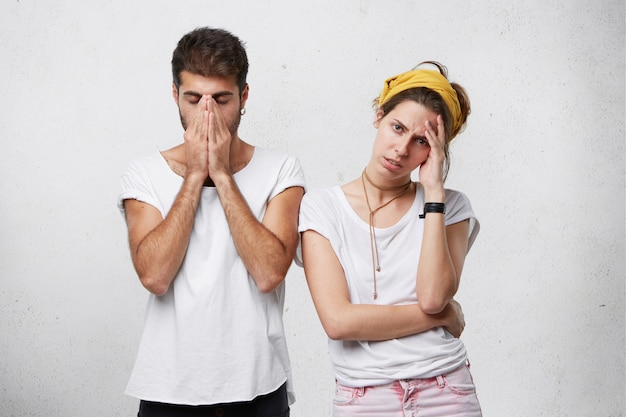 Unhappy depressed young couple feeling stressed, facing financial problems or having argue or dispute: man covering his face while woman touching her forehead, looking frustrated Free Photo