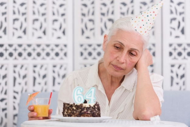 Unhappy elder woman looking at her birthday cake holding glass of juice in hand Free Photo