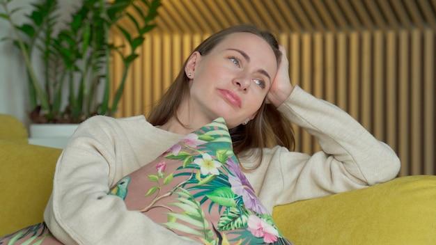 家で不幸な孤独な落ち込んでいる女性、彼女は黄色いソファに座っています Premium写真