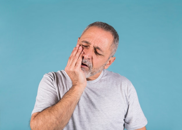 Unhappy man having toothache and touching his cheek Free Photo