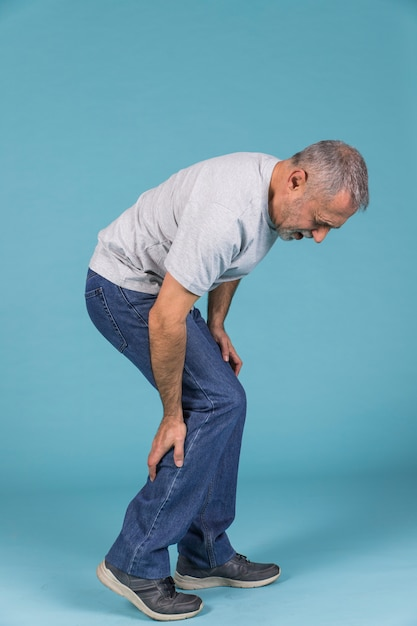 Unhappy man suffering from severe pain on blue wallpaper Free Photo