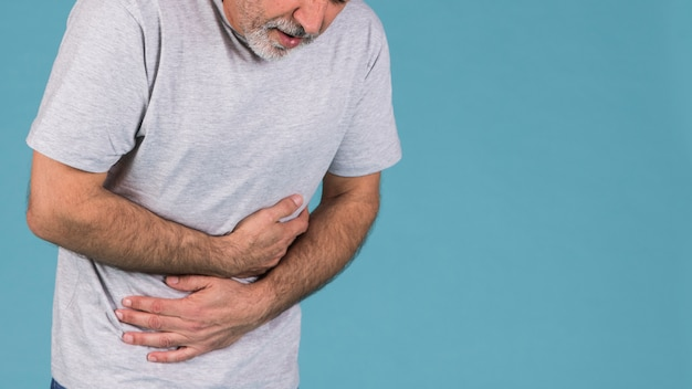 Unhappy man with abdominal pain on blue backdrop Free Photo