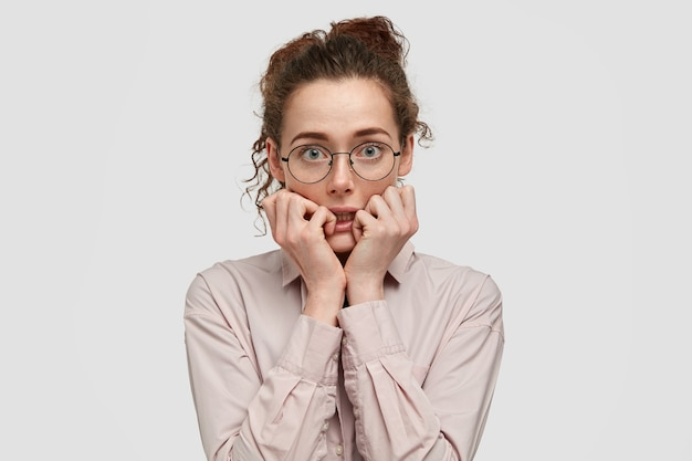 Unhappy nervous young female with worried expression, bites finger nails, looks anxiously directly, wears spectacles, dressed in fashionable clothes, stands against white wall. Free Photo