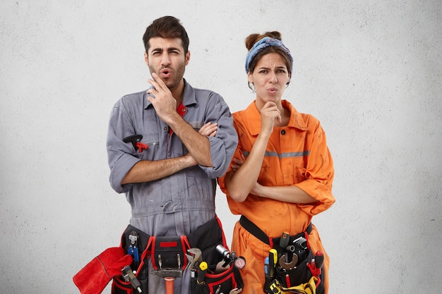 Unhappy plumbing specialists have displeased expression Free Photo