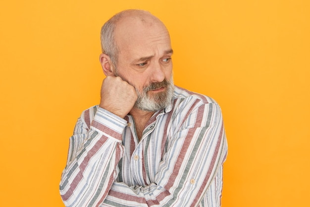 Несчастный пенсионер с седой бородой и облысением позирует изолированно с кулаком на щеке Бесплатные Фотографии