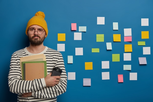 Unhappy schoolboy spends free time on language learning, tries to remember new words with help of sticky notes Free Photo