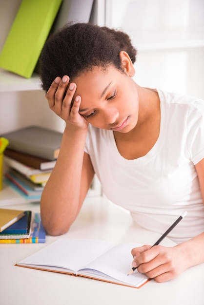 Unhappy schoolgirl sitting at table and writing homework. Premium Photo