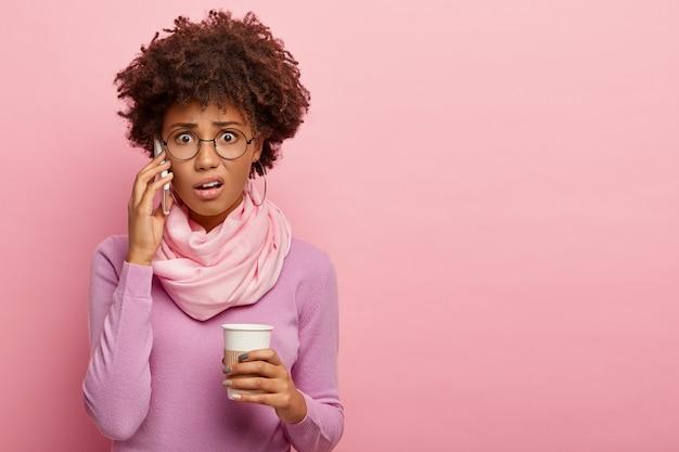 불행한 스트레스에 충격을받은 아프리카 계 미국인 여성이 휴대 전화를 통해 대화하고, 테이크 아웃 커피를 들고, 나쁜 소식을 듣고, 안경과 보라색 폴로 넥을 착용하고, 장미 빛 스튜디오 벽 위에 포즈를 취합니다. 무료 사진