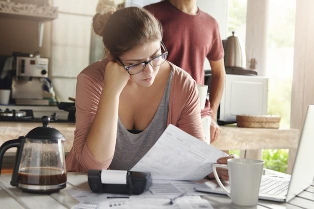 Несчастная подчеркнутая молодая женщина, одетая небрежно, занимается внутренним бюджетом, оплачивает счета онлайн с помощью портативного компьютера, сидит за столом с документами и калькулятором, держит бумагу и внимательно ее читает Бесплатные Фотографии