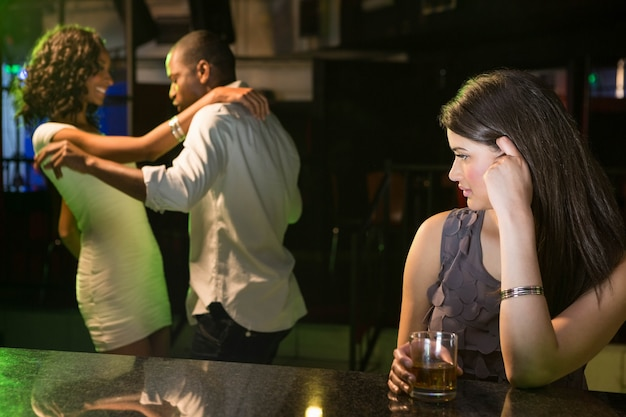 Unhappy woman looking at a couple dancing behind her in bar Premium Photo