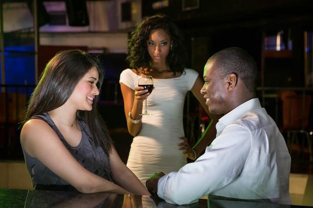 Unhappy woman looking at a couple flirting near bar counter in bar Premium Photo