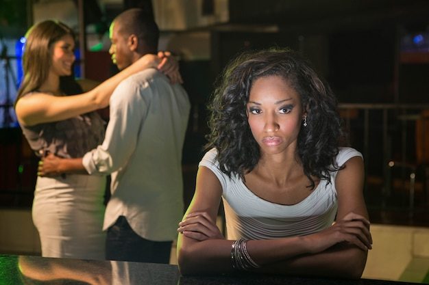Unhappy woman sitting at bar counter and couple dancing behind her in bar Premium Photo