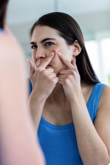Unhappy woman with skin irritation cleaning her face at home Premium Photo