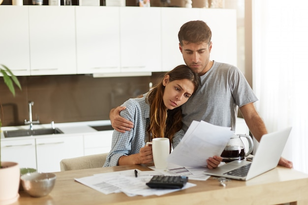 Unhappy young european family facing financial troubles: sad husband deep in thoughts hugging his worried wife who is studying notification from bank in her hands while doing finances in kitchen Free Photo