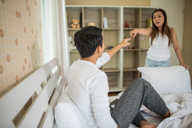 Unhappy young man having argument with his girlfriend in bed room Free Photo