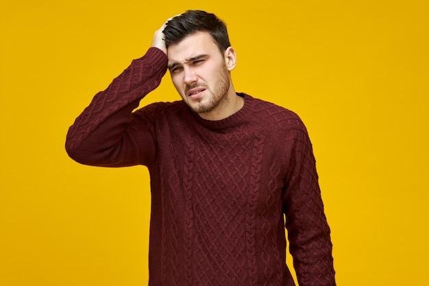 감기, 독감 또는 나쁜 하루를 보내는 따뜻한 스웨터에 불행한 젊은 남자가 두통을 앓고, 아들의 머리를 손에 들고, 온도를 내리기 위해 열병 치료제가 필요합니다. 무료 사진