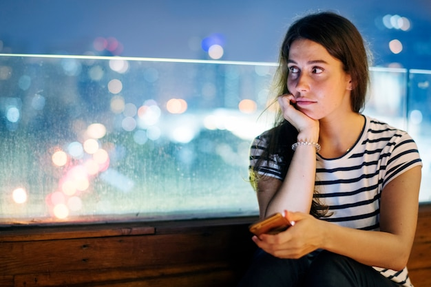 Unhappy young woman holding a smartphone in the evening cityscape Free Photo