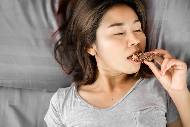 Unhealthy asian woman eating chocolate in bed Premium Photo
