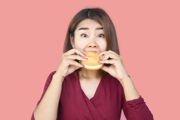 Unhealthy asian woman over eating fast food hamburger Premium Photo