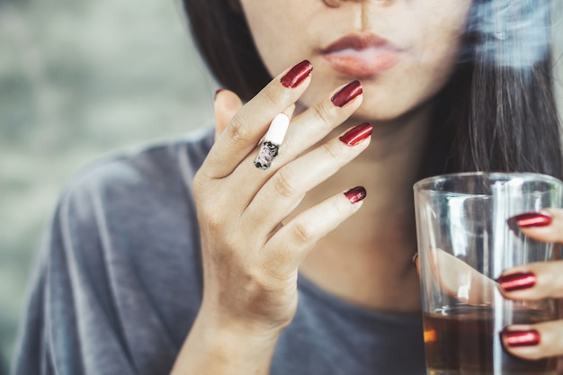 Unhealthy asian woman smoking  and drink alcohol Premium Photo
