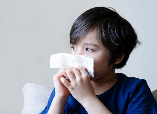 Unhealthy kid with dry skin blowing nose into tissue, child suffering from running nose or sneezing , a boy catches a cold when season change, childhood wiping nose with tissue Premium Photo