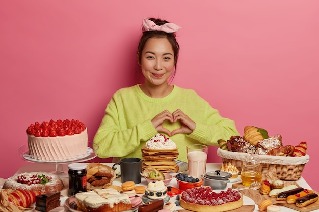 Unhealthy nutrition and calories. pleasant looking asian girl shapes heart over chest, tastes freshly baked homemade confectionery Free Photo