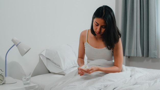 Unhealthy sick indian female suffers from insomnia. asian young woman taking painkiller medicine to relieve headache pain and drink glass of water sitting on bed in her bedroom at home in morning. Free Photo