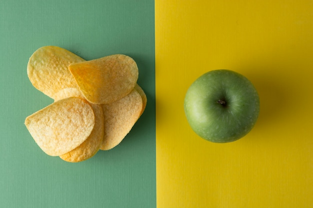 Unhealthy versus healthy food. choise . potatoe chips or green apple for snack. top view, colorful . Premium Photo