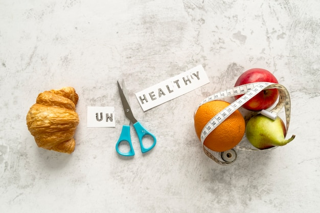 Unhealthy word and scissor with food showing healthy and unhealthy concept Free Photo