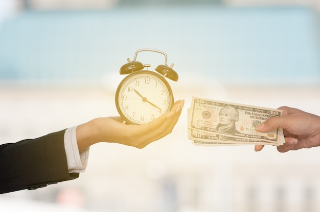 Unidentified business people hands show black alarm clock and dollar bank note Premium Photo