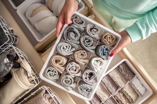 Niezidentyfikowana schludna gospodyni wkłada pojemnik ze skarpetkami, majtkami i bielizną.  przechowywanie ubrań.  Zdjęcie Premium