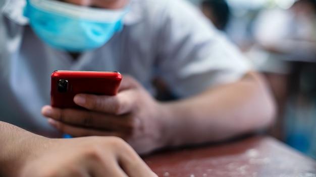 교복 학생들은 스마트 폰을 사용하고 교실에서 보호 마스크를 착용하여 온라인 학습 또는 시험 시험을합니다. 프리미엄 사진
