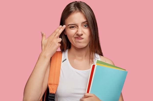 Невпечатленная красивая студентка позирует у розовой стены Бесплатные Фотографии
