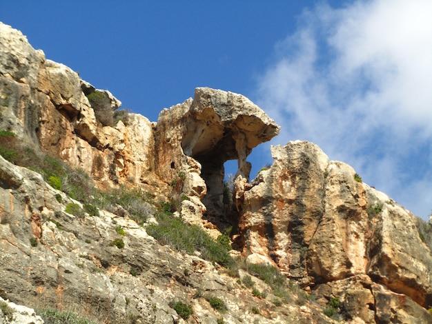 Уникальное естественное формирование тени скал на скале долины вид-бабу на мальте на голубом небе Бесплатные Фотографии