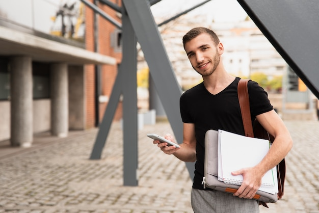 University student holding his notes and phone Free Photo